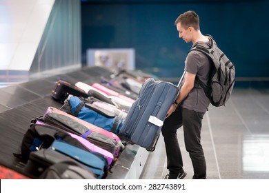 Young handsome man passenger in 20s with carry-on backpack collecting his luggage at conveyor belt in arrivals lounge of airport terminal building