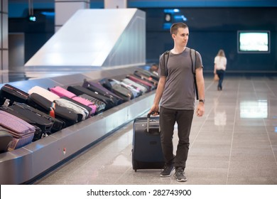 Young handsome man passenger in his 20s walking in arrivals lounge of airport terminal building after collecting his luggage at conveyor belt