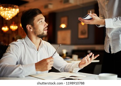 Young handsome man with pen and notepad sitting in cafe and making order with waiter taking notes near