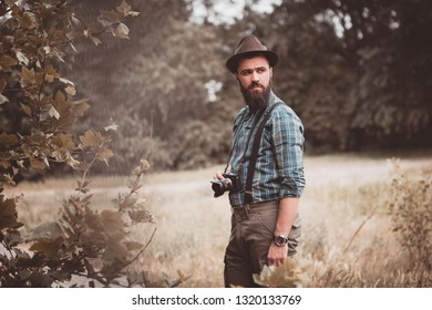 A young and handsome man with a photo camera in the park. Colorized. Cinematic effect.