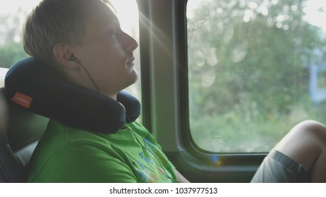 Young handsome man with pillow listening to music while rides on bus
