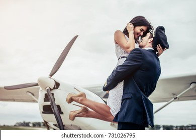 Young handsome man pilot in uniform is standing near small private plane with his beautiful young woman. Couple is hugging and kissing on runway near airplane.