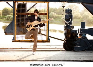 young handsome man play guitar, outdoor shot by the river in harbor