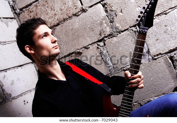 A Young handsome man playing electric guitar
