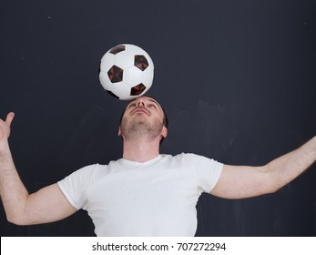 young handsome man playing with soccer ball isolated over grey background