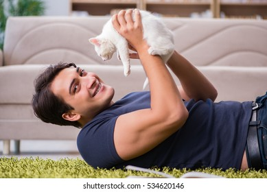 Young handsome man playing with white kitten