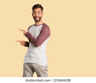 Young handsome man pointing to the side with finger