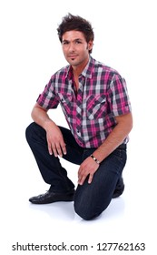 Young handsome man posing to the camera on his knee - isolated
