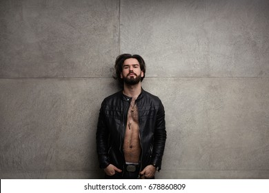 Young handsome man posing in leather jacket on naked torso keeping hands in pockets.