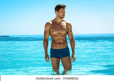 Young handsome man posing in swimming pool