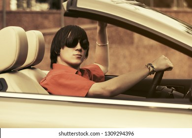 Young handsome man in red shirt and sunglasses driving convertible car