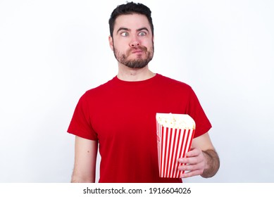 Young handsome man in red T-shirt against white background eating popcorn making grimace and crazy face, screaming out of control, funny lunatic expressing freedom and wild.