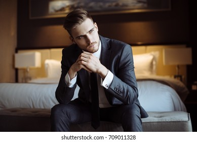 Young handsome man relaxing at his apartment in a hotel after business meeting. Business trip. Booking hotel during your vacation. Businessman in luxury room  of the expensive beautiful hotel.