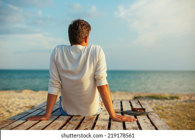 young handsome man relaxing at the sea beach