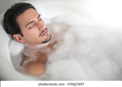 Young handsome man relaxing in the tub