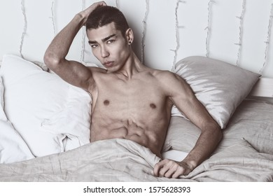 Young handsome man rest in bed. Sexy naked guy is resting