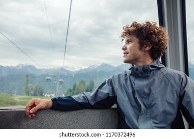 young handsome man is resting in the funicular. awesome ginger tourist going sightseeng with funicular.
