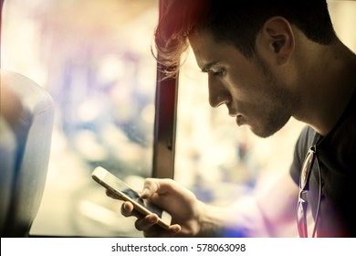 Young handsome man riding bus or pullman texting messages or using cell phone
