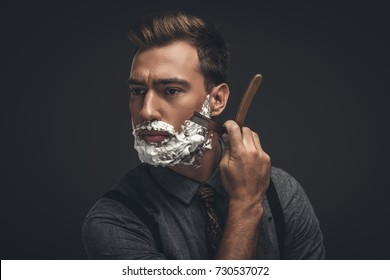 Young handsome man with shaving cream on his face, grooming his beard with straight razor