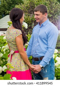Young handsome man in shirt and jeans and a Russian girl in the dress hugging in the park