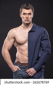 Young handsome man in shirt topless on a black background.