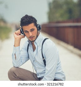 Young handsome man with short hair and beard wearing suspenders and listening to music in an urban context