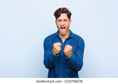 young handsome man shouting aggressively with annoyed, frustrated, angry look and tight fists, feeling furious against blue background
