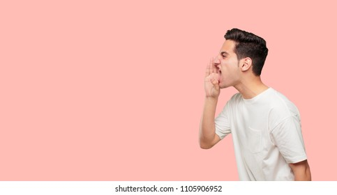 young handsome man shouting loud like crazy, calling with hand with an angry expression, communicating a big announcement. Lateral or side view.