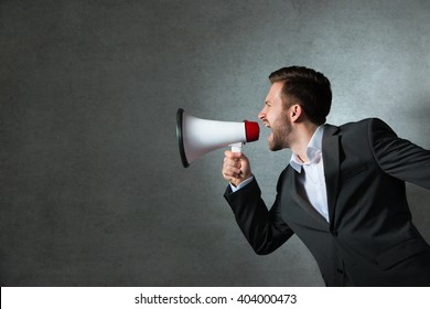 Young handsome man shouting using megaphone over grey background