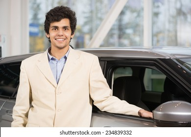 Young handsome man at show room standing near car