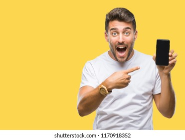 Young handsome man showing smartphone screen over isolated background very happy pointing with hand and finger
