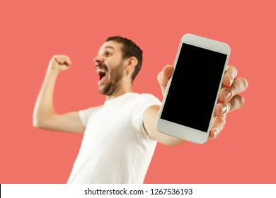 Young handsome man showing smartphone screen over coral background with a surprise face. Human emotions, facial expression concept. Trendy colors