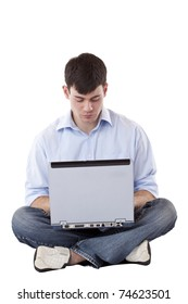 Young handsome man sits with computer on lap and writes an email.Isolated on white background.