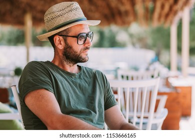 Young handsome man sitting in a beach bar
