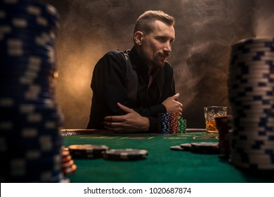 Young handsome man sitting behind poker table with cards and chips