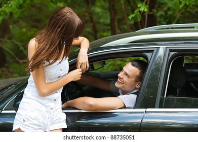 young handsome man sitting car looking out window talking beautiful young woman background summer green park