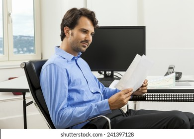 Young handsome man sitting at his desk in the office while reading written agreements and studying important documentation for work