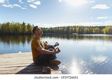 Young handsome man sitting near forest lake, relaxing and meditating in spring or summer sunny day.