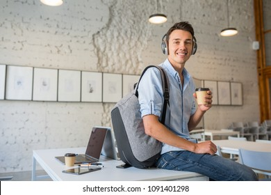young handsome man sitting on table in headphones with backpack in co-working office, drinking coffee, smiling, happy, startup, freelancer, modern office room, open space, workplace, student learning