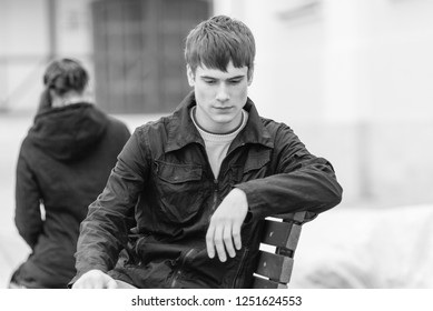 young handsome man sitting on bench, turning away from his girlfriend