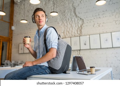 young handsome man sitting on table in headphones with backpack in co-working office drinking coffee, smiling, happy, startup freelancer