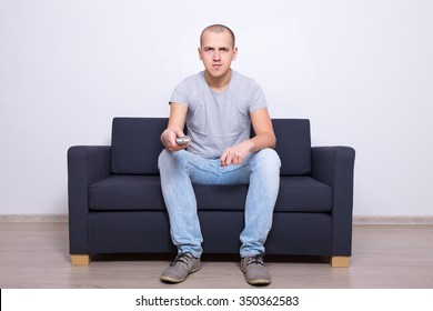 young handsome man sitting on sofa and watching tv at home