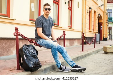 Young handsome man sitting on the street. Dressed in a T-shirt, jeans, fashion sneakers, with a backpack in the form of a lion, sunglasses, Hipster style guy