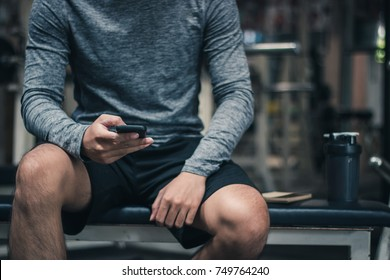 Young handsome man sitting on bench with being used smartphone and side have bottle and note in a gym