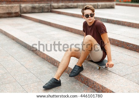 Young handsome man sitting on a skateboard