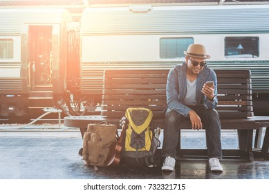 Young handsome man sitting and using smartphone at train station