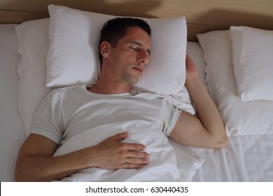 Young handsome man sleeping comfortably in bed.