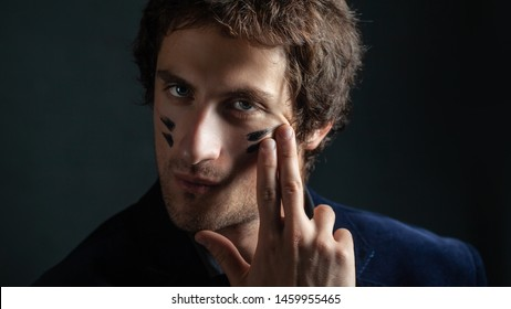 A young handsome man with a slight unshaven face and decisiveness in his eyes, puts a black war paint on his cheeks with his fingers. Portrait on a dark background.