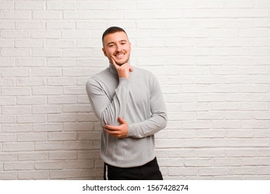 young handsome man smiling happily and daydreaming or doubting, looking to the side against flat background