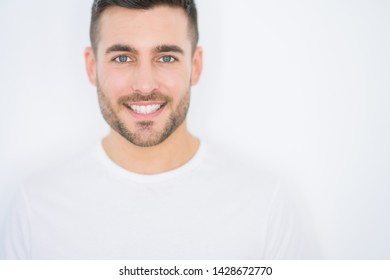 Young handsome man smiling happy wearing casual white t-shirt over white isolated background